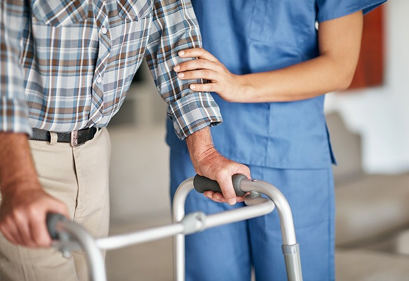 Certified nurse helping man walk with walker
