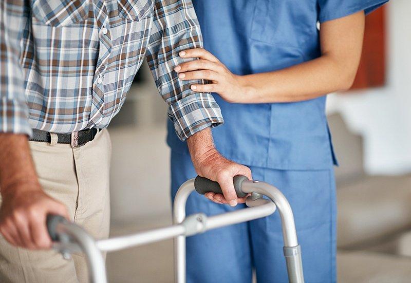 Certified nurse helping man walk with walker
